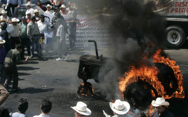 Mexican farmers protesting the removal of import tariffs on U.S. and Canada agricultural goods—as agreed to under the North American Free Trade Agreement (NAFTA)—gather around a tractor set on fire by demonstrators during a protest in Mexico City, Jan. 31, 2008. Photo by Eduardo Verdugo/Associated Press.