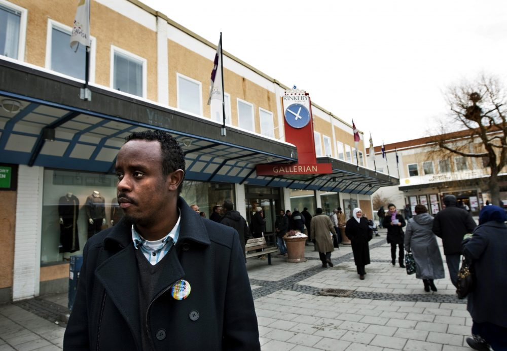 Abadirh Abdi Hussein, 25, a hip hop artist known as Kadafi, watches people crossing a square following Friday prayers in Rinkeby, a largely immigrant suburb of Stockholm, Jan. 22, 2010. Hussein, a Somali immigrant, started a campaign to counter the radicalization of Somali immigrant youth by Islamic extremists. Photo by Christine Olsson/Associated Press.
