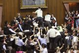 Ruling and opposition lawmakers brawl as discussions start on the Economic Cooperation Framework Agreement (ECFA) planned with China on the legislature floor, July 8, 2010, in Taipei, Taiwan. Lawmakers were seen shoving and punching each other in Taiwan's legislature after the speaker rejected an opposition bid to conduct a detailed debate on a contentious trade pact with China. Photo by Wally Santana/Associated Press.