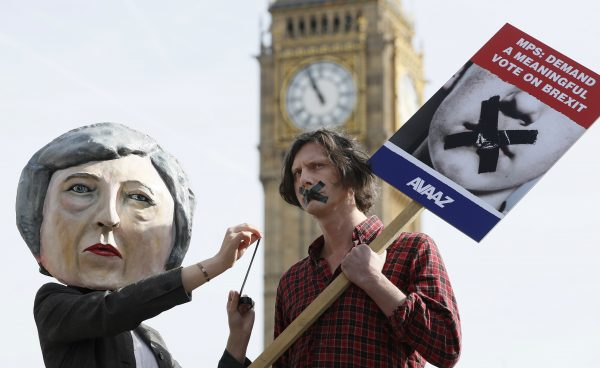 "Demonstrators, one dressed in a Theresa May puppet head, pose near parliament in London, March 13, 2017, to express their concern that the Prime Minister is whipping members of parliament to endorse a ""blank cheque Brexit."" Photo by Kirsty Wigglesworth/Associated Press."