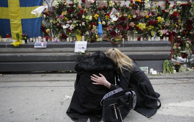 Women mourn at a flower-covered fence near the Ahlens department store following the April 7, 2017 suspected terror attack in central Stockholm. The suspect, Rakhmat Akilov, 39, who was born in Uzbekistan, drove a hijacked truck into a crowd of pedestrians, killing four and injuring 15 others. Uzbekistan's foreign minister said the suspect had been recruited by the Islamic State. Photo by Markus Schreiber/Associated Press.
