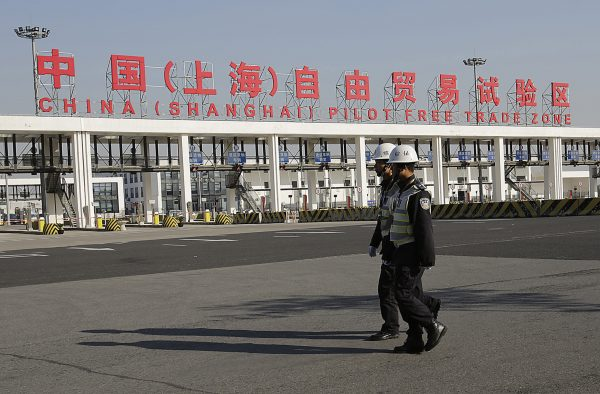 Security guards patrol the main gate of the China (Shanghai) Pilot Free Trade Zone at the Pudong International Airport in Shanghai, China, Nov. 29, 2013. The free trade zone was launched to free up cross-border commodity and capital flows in the world's second largest economy. Photo by Eugene Hoshiko/Associated Press.