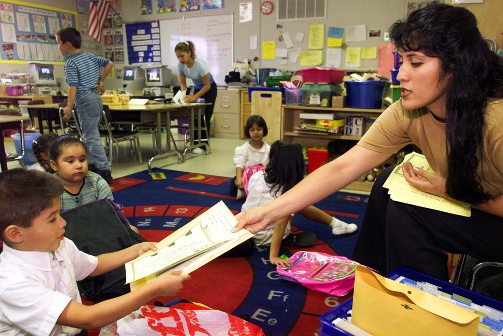 In this file photo, teacher Xochitl Rodriguez hands homework to Marcelo Avila on Sept. 25, 2000, at the Parthenia Elementary School in Sepulveda, Calif. Photo by Damian Dovarganes/Associated Press.