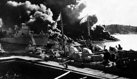 In this Sept. 17, 1941 image, the Swedish destroyer Klas Uggla, No. 4 left, is seen ablaze after an unidentified accident which destroyed the ship, damaged two others, and killed 33 sailors in Horsfjarden, Sweden. The small boats, in foreground, were towed off to safety unharmed. Photo by Associated Press.