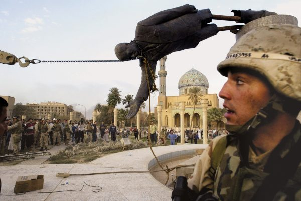 Iraqi civilians and U.S. soldiers pull down a statute of Saddam Hussein in Baghdad, April 9, 2003. Photo by Jerome Delay/Associated Press.