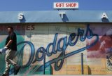 """""""Welcome, Dodger fans! Bring money."""" A man leaves the Dodger Stadium gift shop, June 20, 2011. Photo by Reed Saxon/Associated Press."""