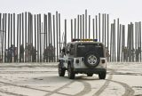 A U.S. Border Patrol vehicle sits parked in front of a crowd of people peering through the U.S.-Mexico border fence at Border Field State Park in San Diego. Border Patrol agents often enter the profession for economic reasons and the relatively good pay, but face dangerous, uncertain, and stressful 24/7 on-call work in remote locations. Many agents also have deep immigrant ties, which can lead to conflicted feelings about their work. Photo by Denis Poroy/Associated Press.
