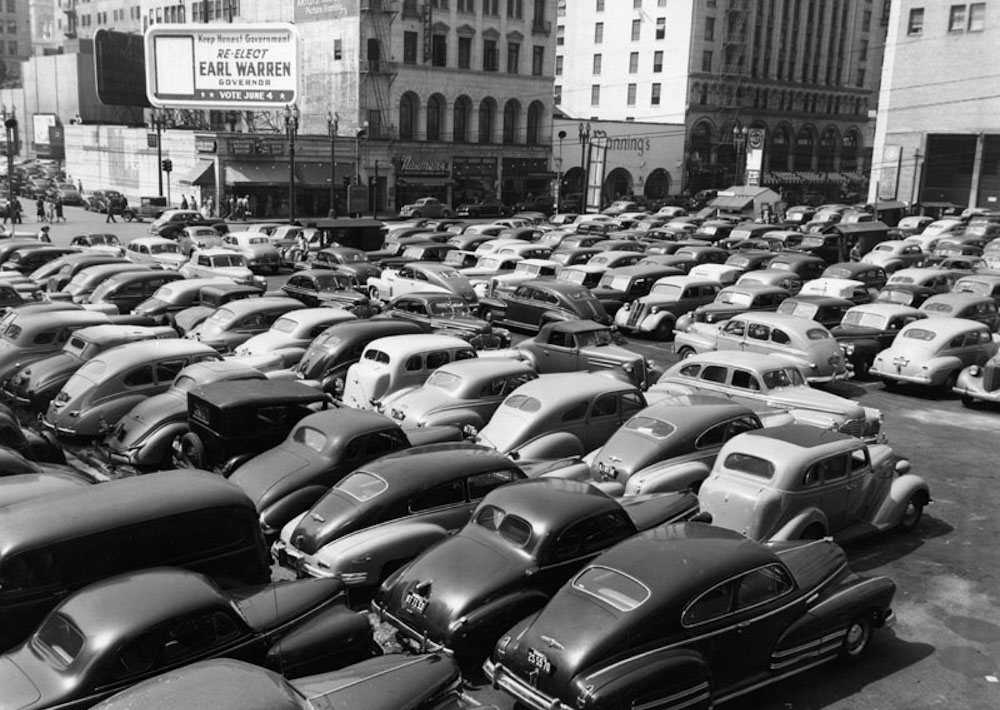 Parking lots on Grand Avenue and Wilshire Blvd. in downtown Los Angeles, May, 1946. A few businesses, such as Dawson's Book Shop (right) and Security First National Bank (left), are visible, as well as a billboard backing re-election for Republican Gov. Earl Warren. Warren helped create California's highway system, which became a model for the U.S. interstate network. Photo courtesy of Los Angeles Public Library.
