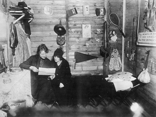 Sitting near a war bonds poster depicting Joan of Arc, Raymonde Breton (R) visits her sister Louise in the Signal Corps barracks at Neufchateau, later bombed by German planes. Photo courtesy of National Archives and Records Administration.