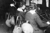 """L-R: Berthe Hunt, Esther """"Tootsie"""" Fresnel, and Grace Banker run Gen. John Pershing's switchboard at First Army headquarters. Note the helmets and gas masks hanging from their chairs. Photo courtesy of National Archives and Records Administration."""